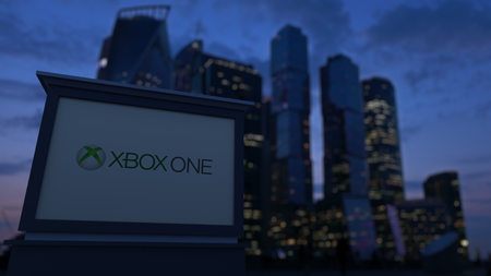 xbox: Street signage board with Xbox One logo in the evening. Blurred business district skyscrapers background. Editorial 3D United States
