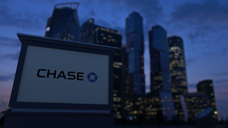 Street signage board with JPMorgan Chase Bank logo in the evening. Blurred business district skyscrapers background. Editorial 3D United States
