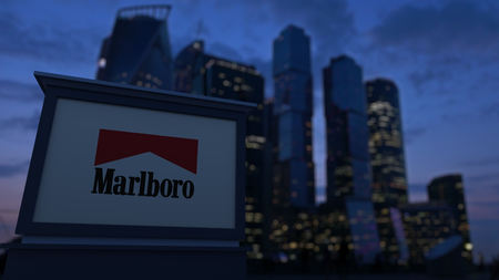 Street signage board with Marlboro logo in the evening. Blurred business district skyscrapers background. Editorial 3D United States