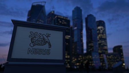 nestle: Street signage board with Nestle logo in the evening. Blurred business district skyscrapers background. Editorial 3D United States Editorial