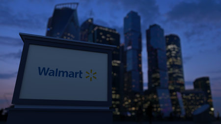 Street signage board with Walmart logo in the evening. Blurred business district skyscrapers background. Editorial 3D United States