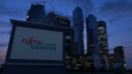 Street signage board with Fujitsu Siemens Computers logo in the evening. Blurred business district skyscrapers background. Editorial 3D United States