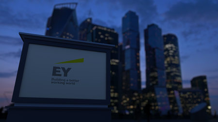 lawer: Street signage board with Ernst & Young logo in the evening. Blurred business district skyscrapers background. Editorial 3D United States