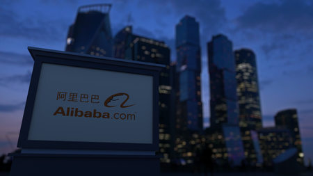 alibaba: Street signage board with Alibaba.com logo in the evening. Blurred business district skyscrapers background. Editorial 3D United States