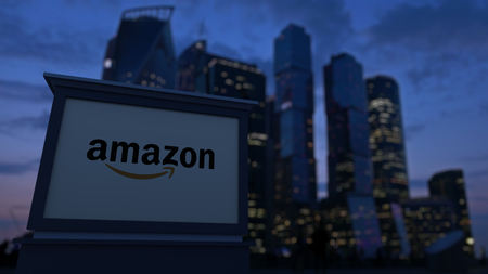 Street signage board with Amazon.com logo in the evening. Blurred business district skyscrapers background. Editorial 4K clip, ProRes