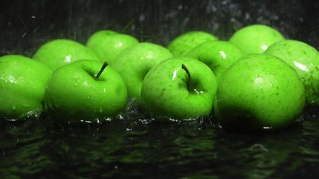 green apples: Green apples being washed, dark background