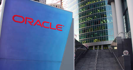 oracle: Street signage board with Oracle Corporation logo. Modern office center skyscraper and stairs background. Editorial 3D rendering United States