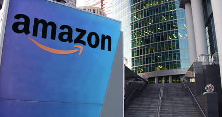 Street signage board with Amazon.com logo. Modern office center skyscraper and stairs background. Editorial 3D rendering United States