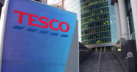 Tesco 로고가있는 거리 표지판. 현대 사무실 센터 마천루와 계단 배경입니다. Editorial 3D rendering 미국
