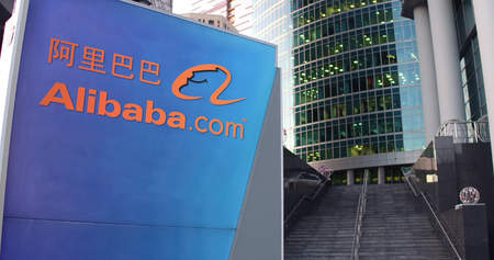 Street signage board with Alibaba.com logo. Modern office center skyscraper and stairs background. Editorial 3D rendering United States Editorial