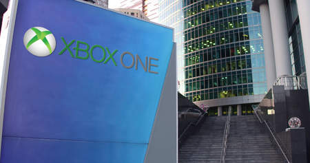 xbox: Street signage board with Xbox One logo. Modern office center skyscraper and stairs background. Editorial 3D rendering United States Editorial