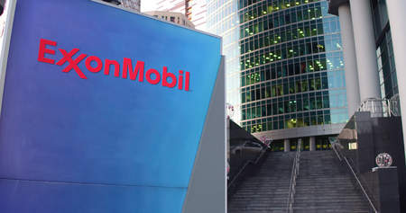 Street signage board with ExxonMobil logo. Modern office center skyscraper and stairs background. Editorial 3D rendering United States