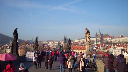 distant work: PRAGUE, CZECH REPUBLIC - DECEMBER 3, 2016. Charles bridge and distant Prague castle on a sunny day. Walking tourists and street artists at work