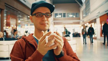 to get warm: Nerdy man in black rim glasses having big cup of coffee at the airport cafe