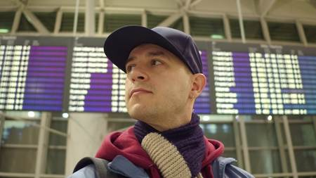 Caucasian man wearing cap looks around near airport terminal departure board. Tourism or travel concepts