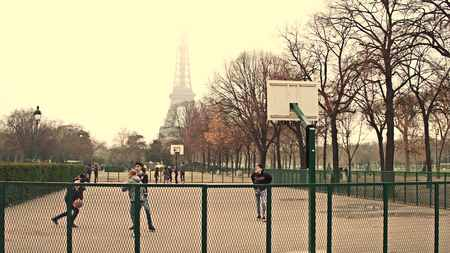 colores calidos: PARIS, FRANCE - DECEMBER, 31, 2016. Multinatonal male teenagers playing street basketball against Eiffel Tower on a foggy day, warm colors
