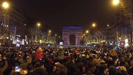 champs elysees: PARIS, FRANCE - DECEMBER, 31, 2016. Overhead shot of crowded Champs-Elysees street and light show on famous triumphal arch, Arc de Triomphe. New Years eve