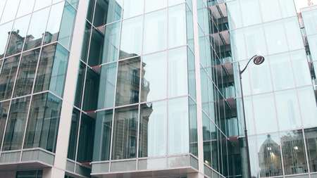 distort: Distorted reflection of old building in modern office glass facade in Paris. Opposites concept