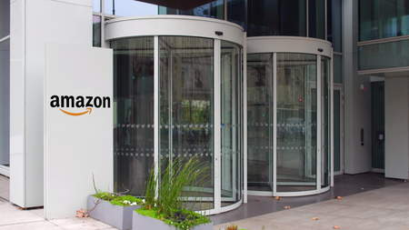 Street signage board with Amazon.com logo. Modern office building. Editorial 3D rendering