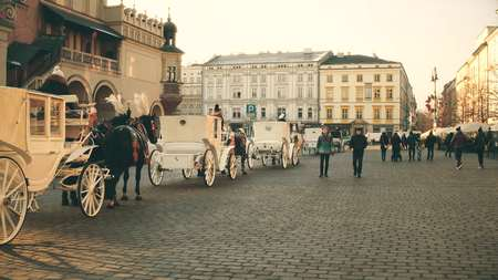 colores calidos: KRAKOW, POLAND - JANUARY, 14, 2017 Retro horse drawn carriages and Old town street, warm colors