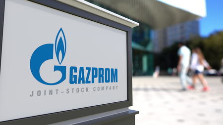 Street signage board with Gazprom logo. Blurred office center and walking people background. Editorial 3D rendering