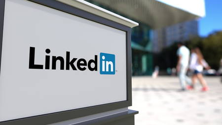 Street signage board with LinkedIn logo. Blurred office center and walking people background. Editorial 3D rendering Editorial