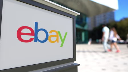 ebay: Street signage board with eBay Inc. logo. Blurred office center and walking people background. Editorial 3D rendering
