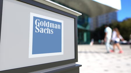 Street signage board with The Goldman Sachs Group, Inc. logo. Blurred office center and walking people background. Editorial 3D rendering