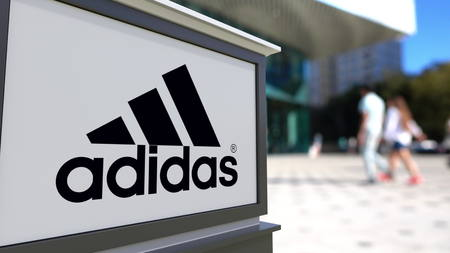 adidas: Street signage board with Adidas inscription and logo. Blurred office center and walking people background. Editorial 3D rendering Editorial