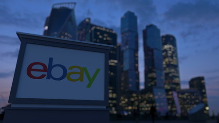 ebay: Street signage board with eBay Inc. logo in the evening.  Blurred business district skyscrapers background. Editorial 3D rendering
