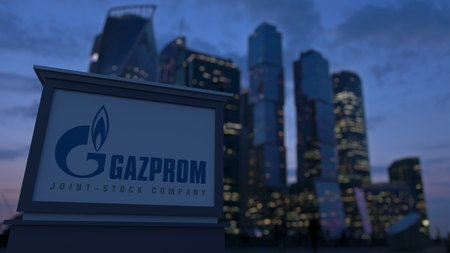 Street signage board with Gazprom logo in the evening.  Blurred business district skyscrapers background. Editorial 3D rendering