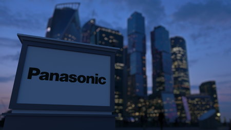 Street signage board with Panasonic Corporation logo in the evening.  Blurred business district skyscrapers background. Editorial 3D rendering Editorial