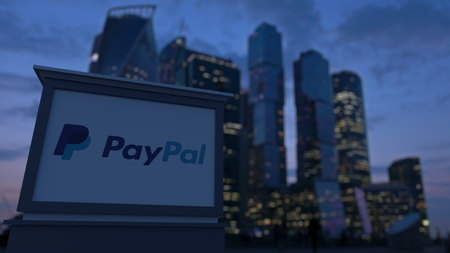 paypal: Street signage board with PayPal logo in the evening.  Blurred business district skyscrapers background. Editorial 3D rendering