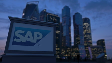 Street signage board with SAP SE logo in the evening.  Blurred business district skyscrapers background. Editorial 3D rendering Editorial