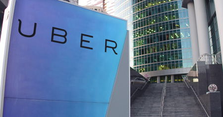 Street signage board with Uber Technologies Inc. logo. Modern office center skyscraper and stairs background. Editorial 3D rendering