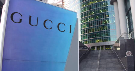 gucci store: Street signage board with Gucci logo. Modern office center skyscraper and stairs background. Editorial 3D rendering