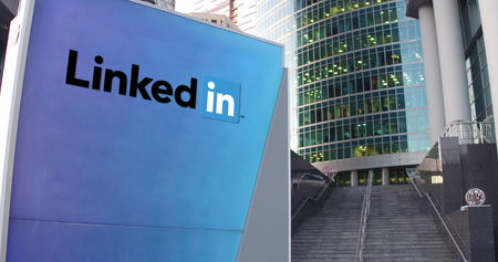 Street signage board with LinkedIn logo. Modern office center skyscraper and stairs background. Editorial 3D rendering