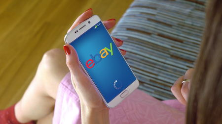 ebay: Young woman holding a cell phone with loading Ebay mobile app. Conceptual editorial CGI