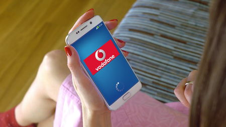 Young woman holding a cell phone with loading Vodafone mobile app. Conceptual editorial CGI