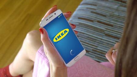 Jonge vrouw met een mobiele telefoon met het laden Ikea mobiele app. Conceptuele redactionele CGI