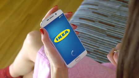 Young woman holding a cell phone with loading Ikea mobile app. Conceptual editorial CGI