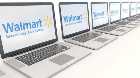 Modern laptops with Walmart logo. Computer technology conceptual editorial 3D