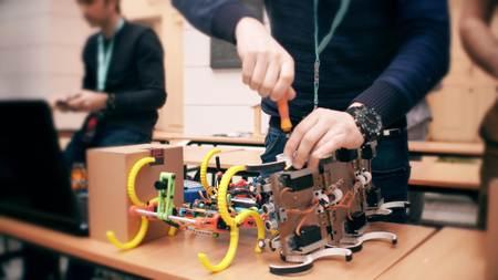 Young man repairing DIY robot