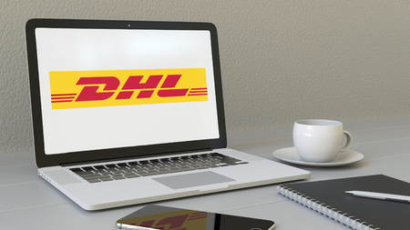 Laptop with DHL Express logo on the screen. Modern workplace conceptual editorial 4K animation