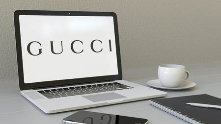 Laptop with Gucci logo on the screen. Modern workplace conceptual editorial 4K animation