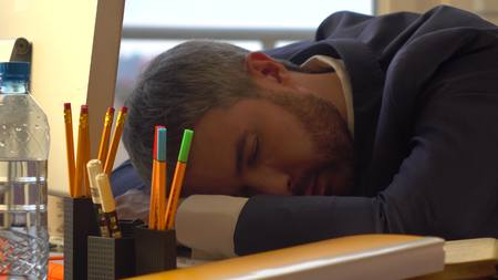 Young bearded businessman sleeping in the morning at his workplace after working overnight