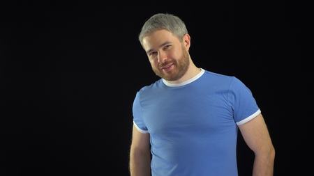 smiing: Athletic bearded man in blue t-shirt smiing at the camera against black background