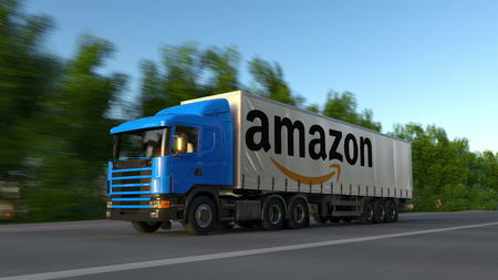 Freight semi truck with Amazon.com logo driving along forest road. Editorial 3D rendering
