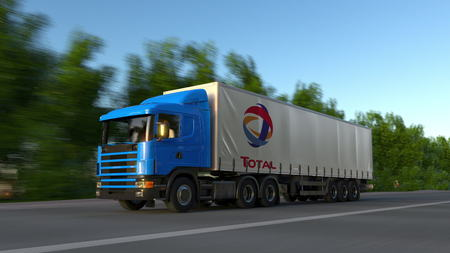 Freight semi truck with Total S.A. logo driving along forest road. Editorial 3D rendering Redakční