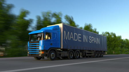Speeding freight semi truck with MADE IN SPAIN caption on the trailer. Road cargo transportation. 3D rendering